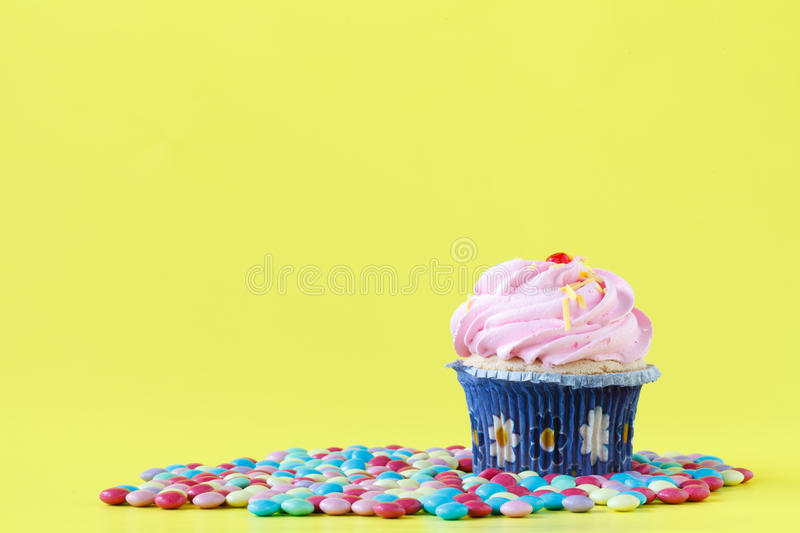 Tasty cupcakes with candles on colorful background royalty free stock photography