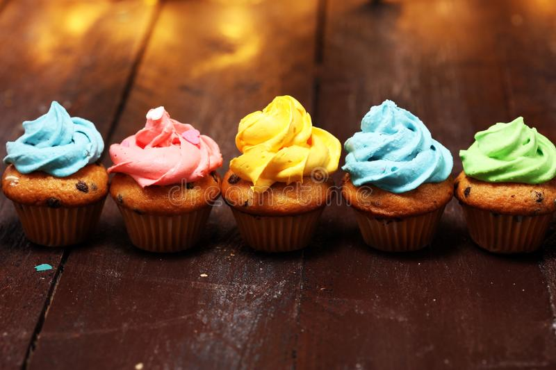 Tasty cupcakes on christmas winter background. Birthday cupcake. In rainbow colors royalty free stock image
