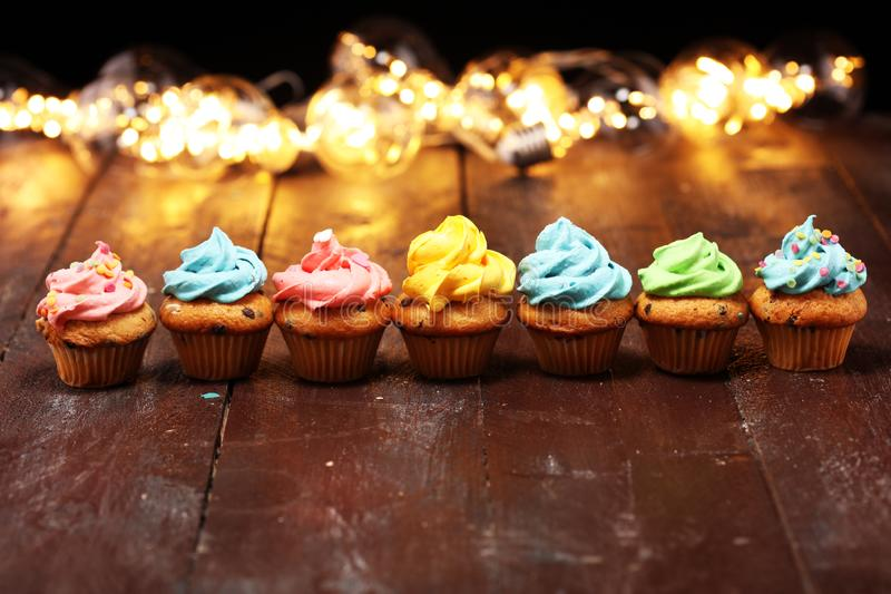 Tasty cupcakes on christmas winter background. Birthday cupcake. In rainbow colors royalty free stock photography