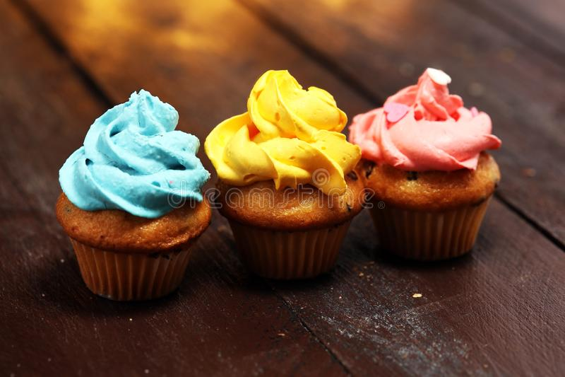 Tasty cupcakes on christmas winter background. Birthday cupcake. In rainbow colors royalty free stock images