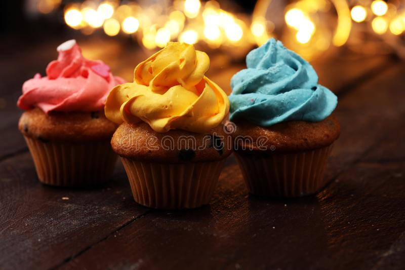 Tasty cupcakes on christmas winter background. Birthday cupcake. In rainbow colors stock photography