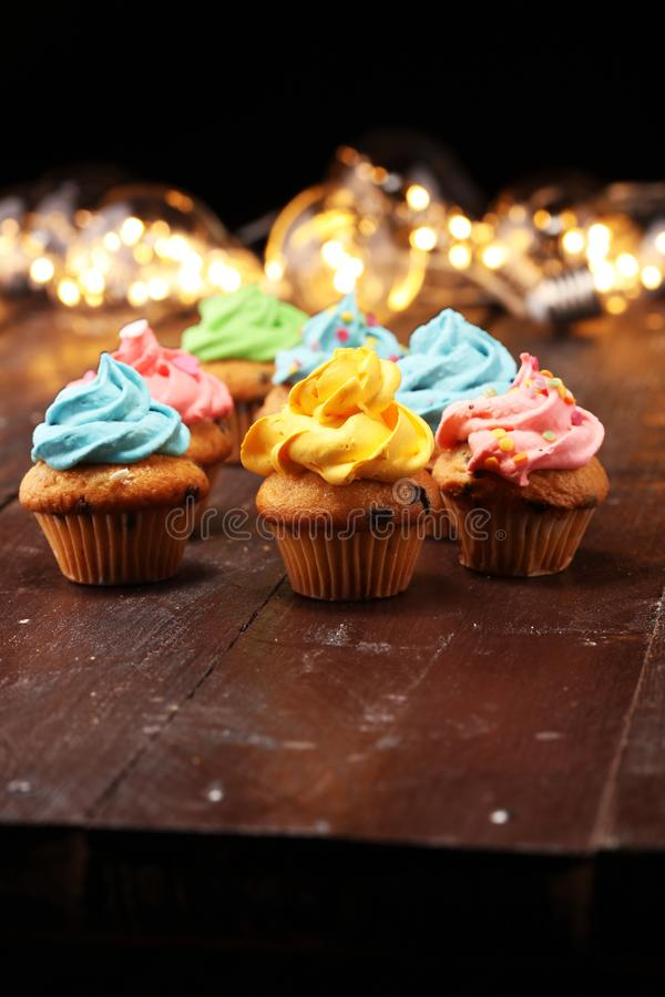 Tasty cupcakes on christmas winter background. Birthday cupcake. In rainbow colors royalty free stock photos