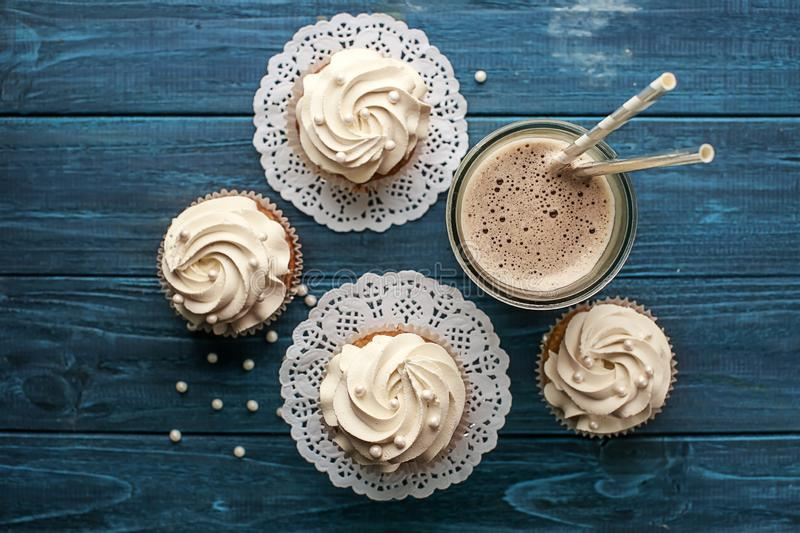 Tasty cupcakes and glass of drink on wooden table stock photography