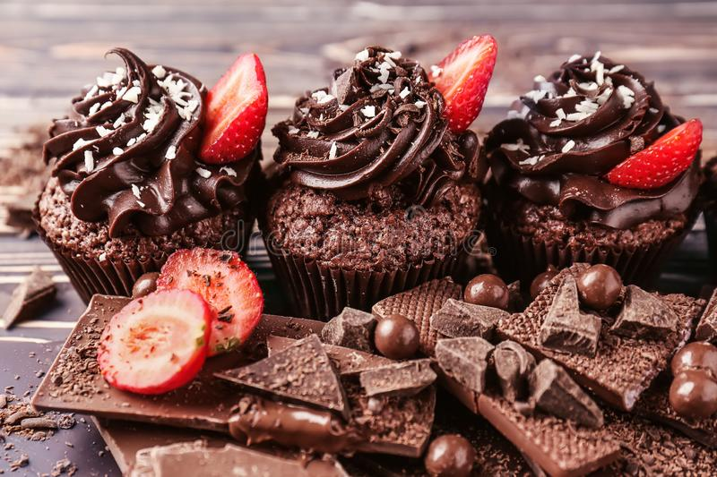 Tasty cupcakes with strawberry and pieces of chocolate bar on wooden table royalty free stock images