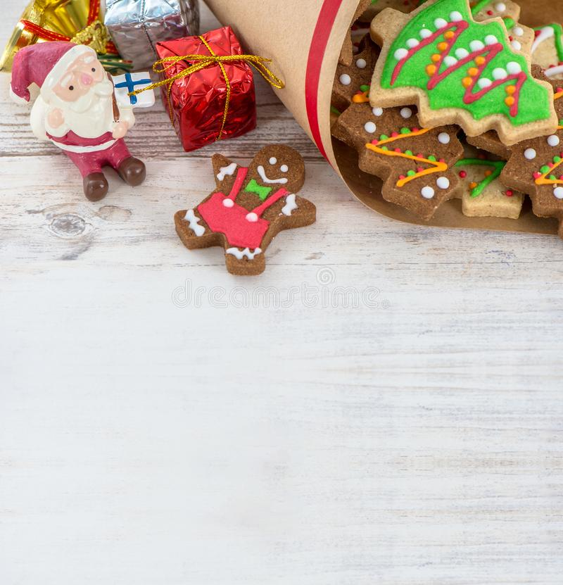 Tasty and cute baked Christmas cookies gingerbread. With beautiful xmas decoration in paper bag on light wooden table background, close up, copy space text stock images