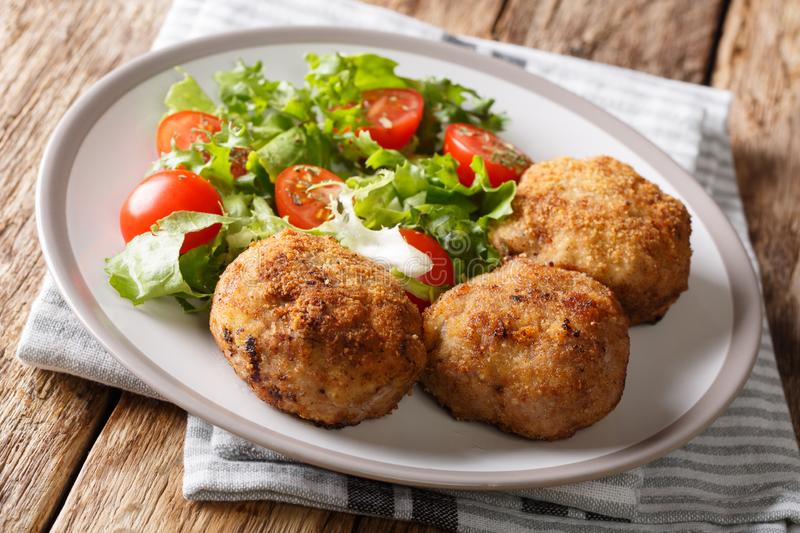 Tasty Danish pork minced meat patties in breading with fresh veg. Etable salad close-up on a plate on the table. horizontal royalty free stock images