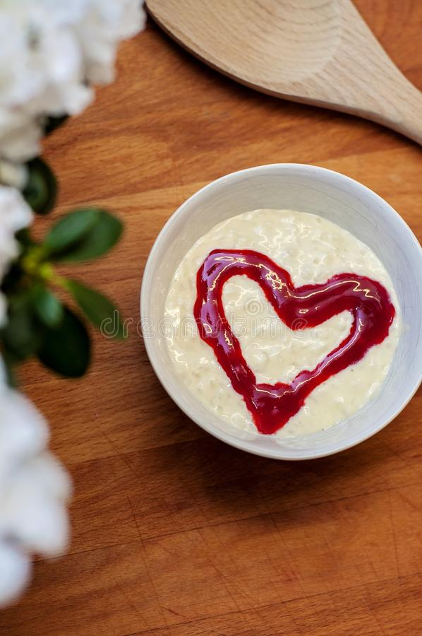 Tasty and delicious rice pudding with a red raspberry heart in the middle, on a wooden cutboard. A traditional Christmas dessert stock images