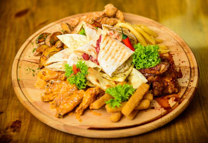 Tasty delicious snacks. Snack for beer. Restaurant food. Wooden board with lot french fries fish sticks burrito and meat royalty free stock images