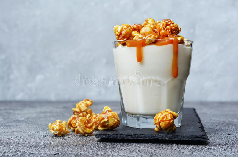Tasty dessert. Glass of homemade yogurt with caramel popcorn and sweet sauce on black slate board. On gray concrete background royalty free stock image
