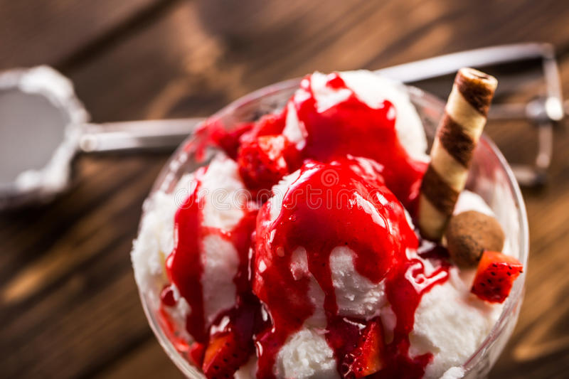 Tasty dessert of ice cream with sirup and waffle. Tasty sweet dessert of ice cream poured with berry sirup in glass ramekin on wooden table. From above royalty free stock photos