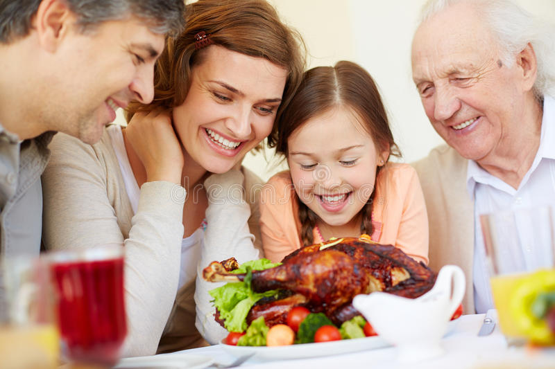 Tasty dish. Family of four around roasted chicken in anticipation royalty free stock photos