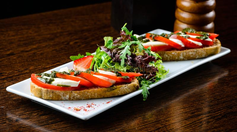 Tasty dish in a restaurant. Slice of bread served with fresh tom. Atoes and cheese stock photo