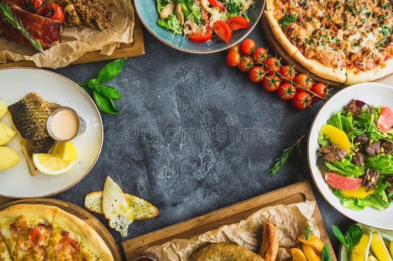 Tasty dishes on dark table. Grilled pork ribs, pizza, salads, fish and sausages with fried potatoes. Flat lay. Top view. Food fram stock images