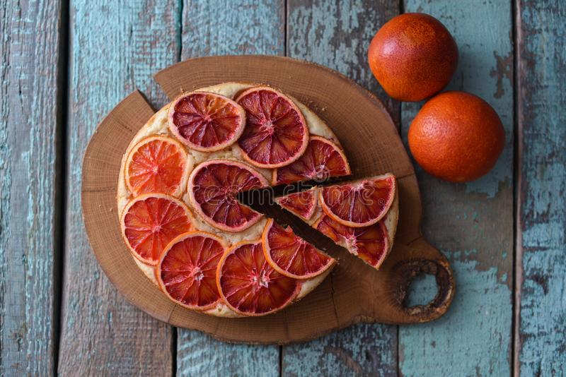 Tasty domestic dessert. Juicy blood orange cake on oak cutting b. Oard over rustic shabby blue background copyspace top view stock images