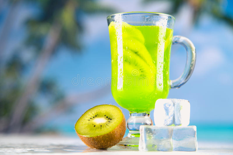 Tasty drink with kiwi on sandy beach.  stock photos