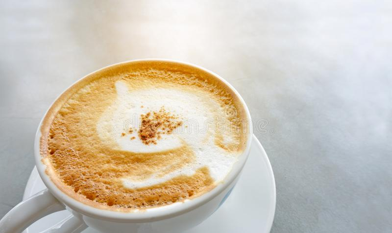 Tasty drinking, a cup of cappuccino coffee decorated with fluffy white and brown milk froth in white ceramic cup on gray table, stock images