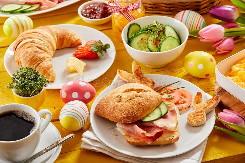 Tasty Easter brunch or spring breakfast. With a fresh croissant, ham or bacon roll and coffee on a table decorated with colorful Easter eggs and tulips royalty free stock photo