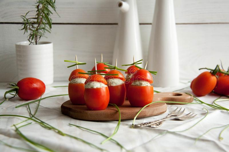 Stuffed tomato with chicken, garlic and cream cheese pasta lying on a brown wooden board stock photography