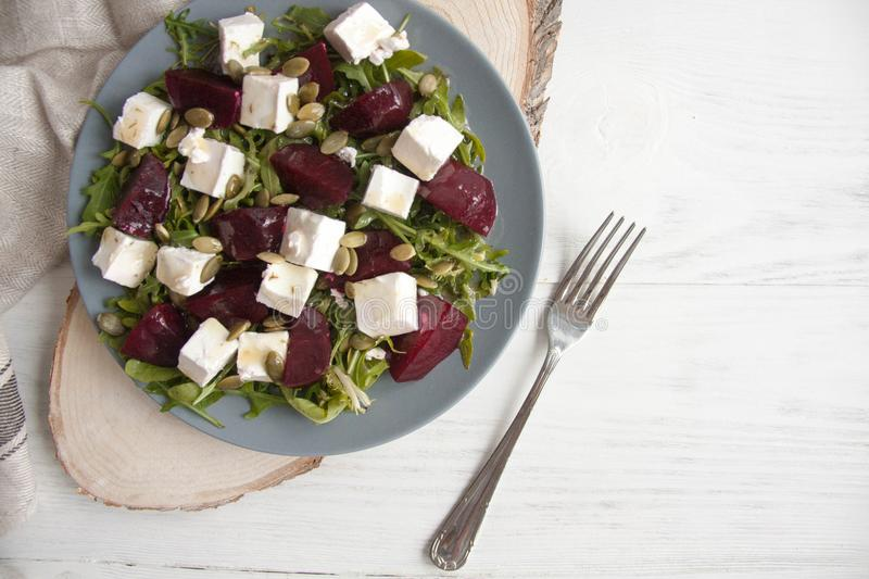 Salad with beets, feta cheese and pumpkin seeds on a gray plate. Tasty and easy lunch or appetizer idea: Salad with beets, feta cheese and pumpkin seeds on a stock images