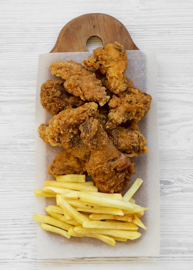 Tasty fastfood: fried chicken drumsticks, spicy wings, French fries and chicken tenders on rustic wooden board over white wooden. Background, top view. Flat lay stock photos