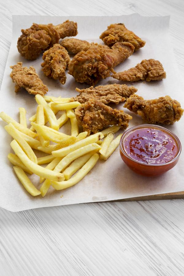 Tasty fastfood: fried chicken drumsticks, spicy wings, French fries and chicken tenders with sour-sweet sauce on baking sheet over. White wooden surface stock photo