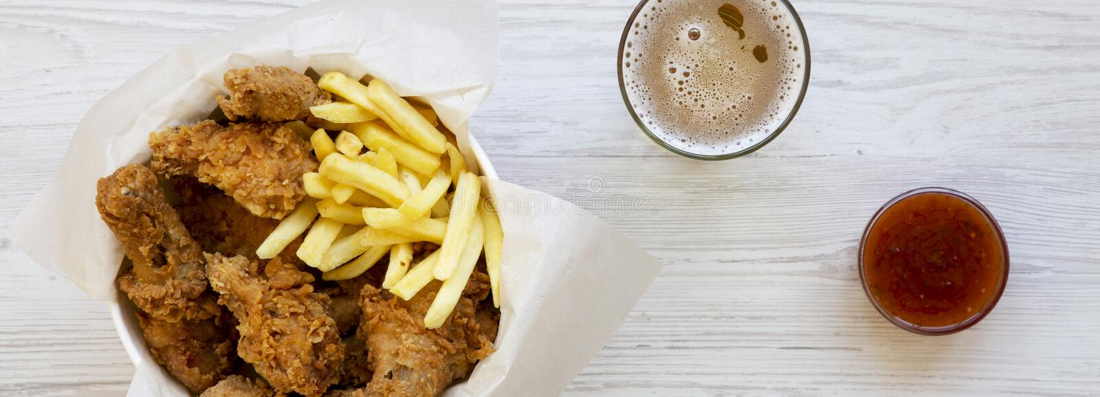 Tasty fastfood: fried chicken drumsticks, spicy wings, French fries and chicken tenders in paper box, sauce and cold beer on a. White wooden surface, overhead royalty free stock photos