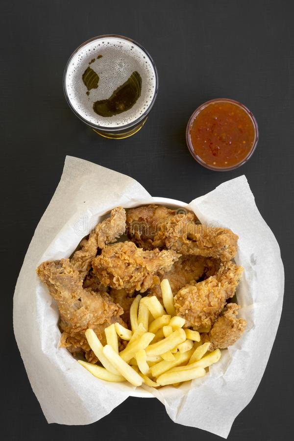 Tasty fastfood: fried chicken drumsticks, spicy wings, French fries and chicken tenders in paper box, sour-sweet sauce, cold beer. On black surface, top view stock image
