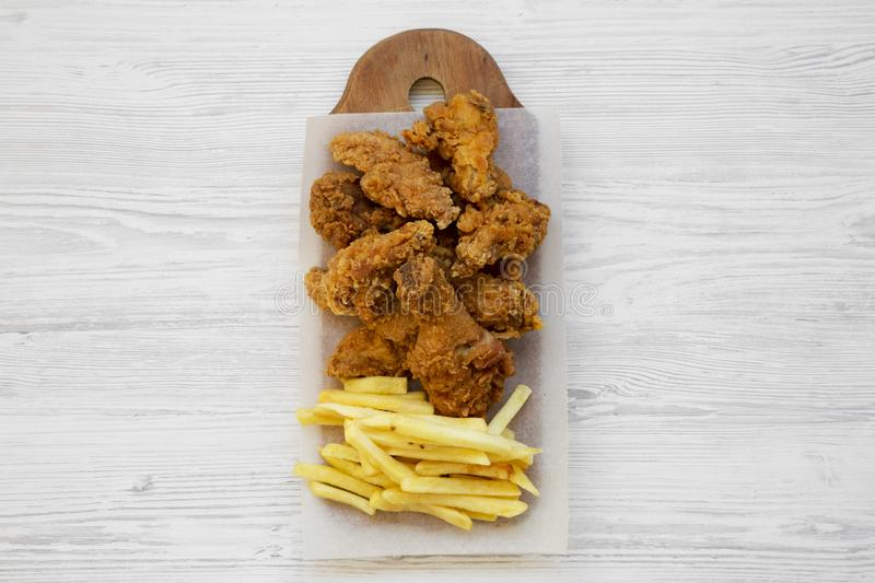 Tasty fastfood: fried chicken legs, spicy wings, French fries and chicken tenders on rustic wooden board over white wooden surface. Top view. Flat lay stock photo
