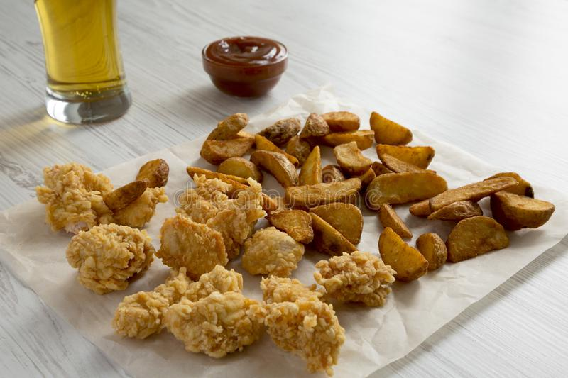 Tasty fastfood: fried potato wedges, chicken bites, barbecue sauce and glass of beer on a white wooden surface, side view. Closeup royalty free stock photos