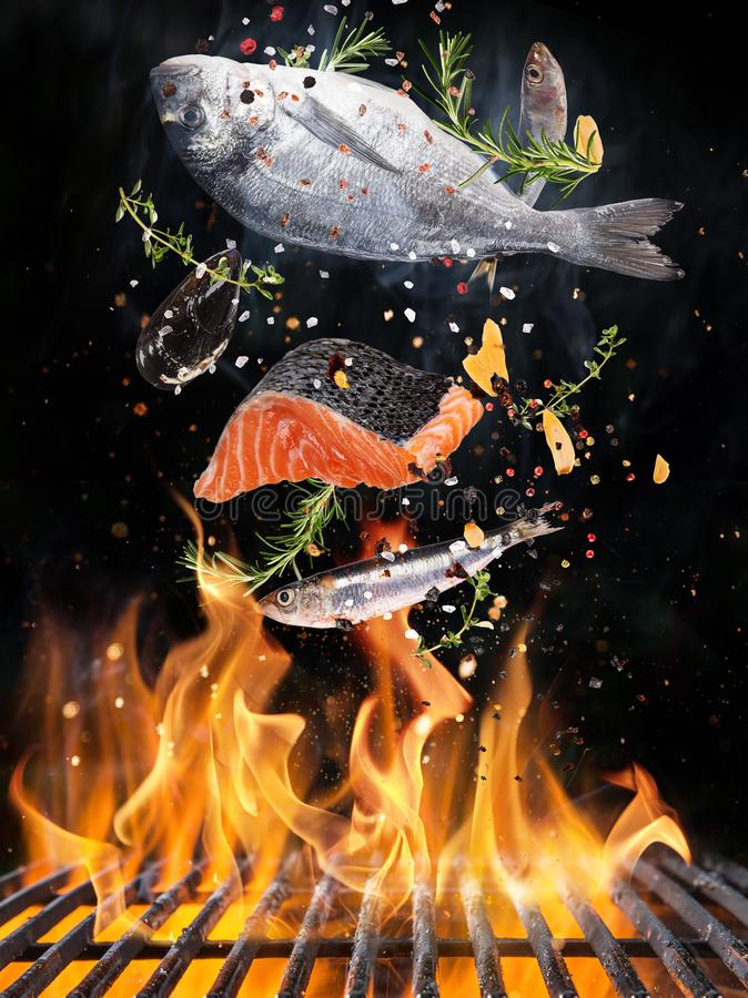 Tasty fishes flying above cast iron grate with fire flames. stock photography