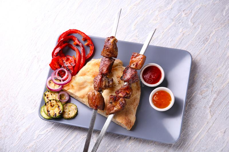 Tasty flatbread with pieces of shish-kebab, vegetables and sauces on plate stock images