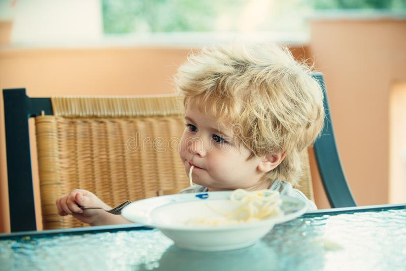 Tasty food, cute child eating spaghetti. The child in the kitchen at the table eating pasta. Italian food for children. royalty free stock image