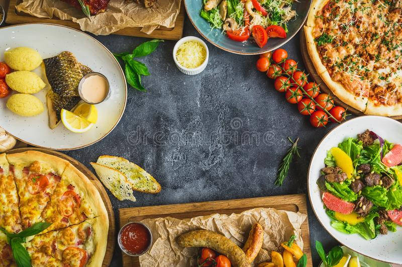 Tasty food on dark table. Grilled pork ribs, pizza, salads, fish and sausages with fried potatoes. Flat lay. Top view. Food frame, royalty free stock photos