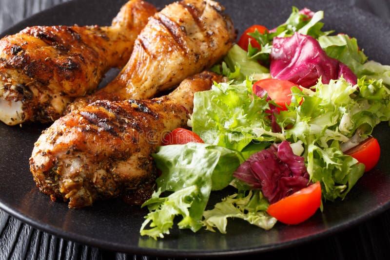 Tasty food: serving of grilled chicken drumsticks and fresh vegetable salad close-up. horizontal stock image