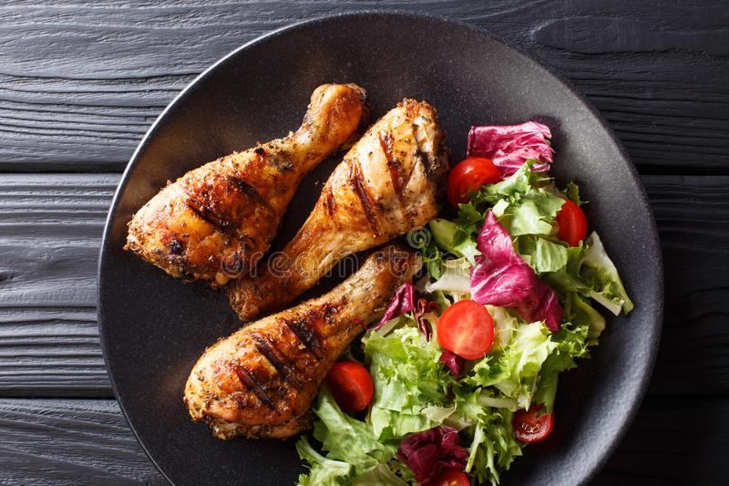 Tasty food: serving of grilled chicken drumsticks and fresh vegetable salad close-up. Horizontal top view royalty free stock image