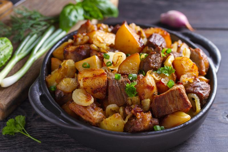 Tasty food: succulent beef with fried potatoes, onion and garlic. Country-style roasted potatoes with meat. royalty free stock photo