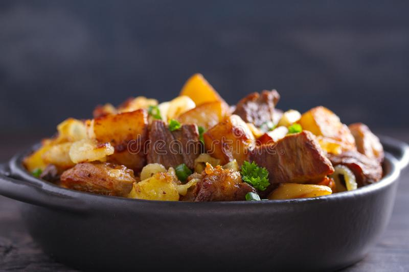 Tasty food: succulent beef with fried potatoes, onion and garlic. Country-style roasted potatoes with meat. stock photo