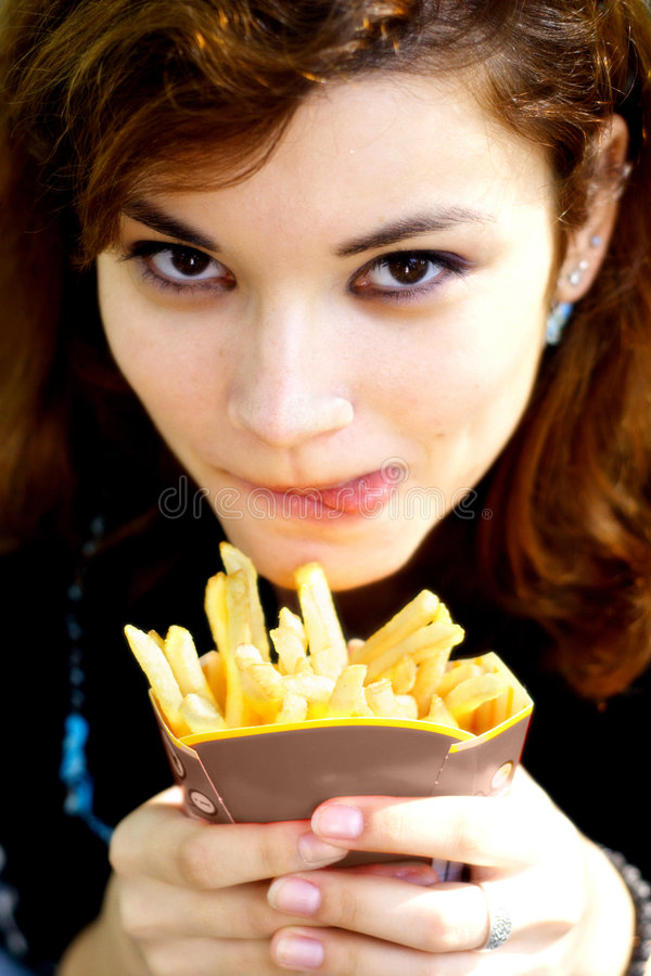 Tasty french fries. Pretty girl with tasty french fries licking her lips royalty free stock photo