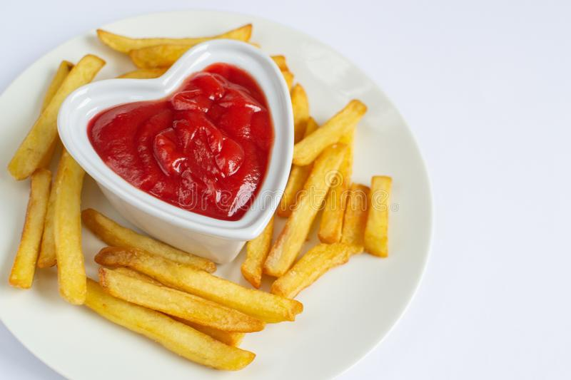Tasty french fries on white plate with heart pattern of ketchup stock photo
