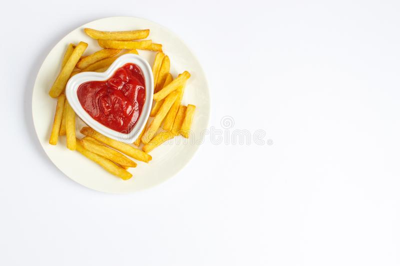 Tasty french fries on white plate with heart pattern of ketchup. White background, Valentines day stock photo