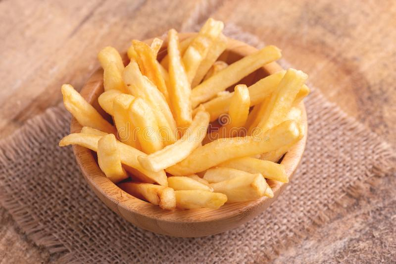 Tasty french fries in wooden bowl on burlap napkin stock images