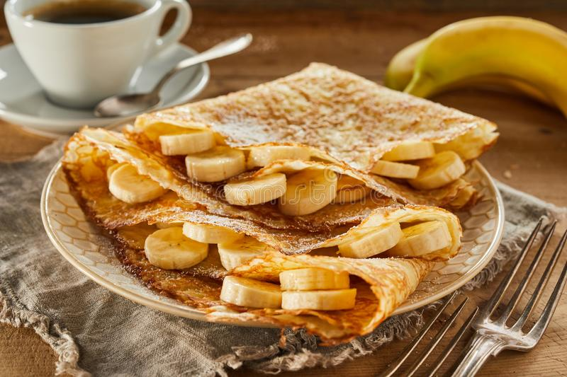 Tasty fresh banana pancakes or wraps with coffee. Tasty fresh banana golden fried pancakes or wraps served with coffee for a healthy rustic breakfast in a close stock photo