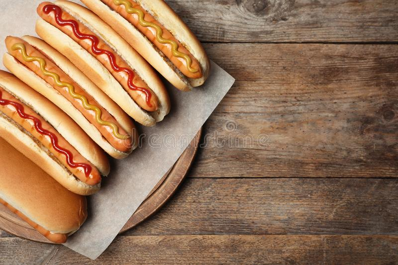 Tasty fresh hot dogs on wooden table, top view. Space for text royalty free stock photos
