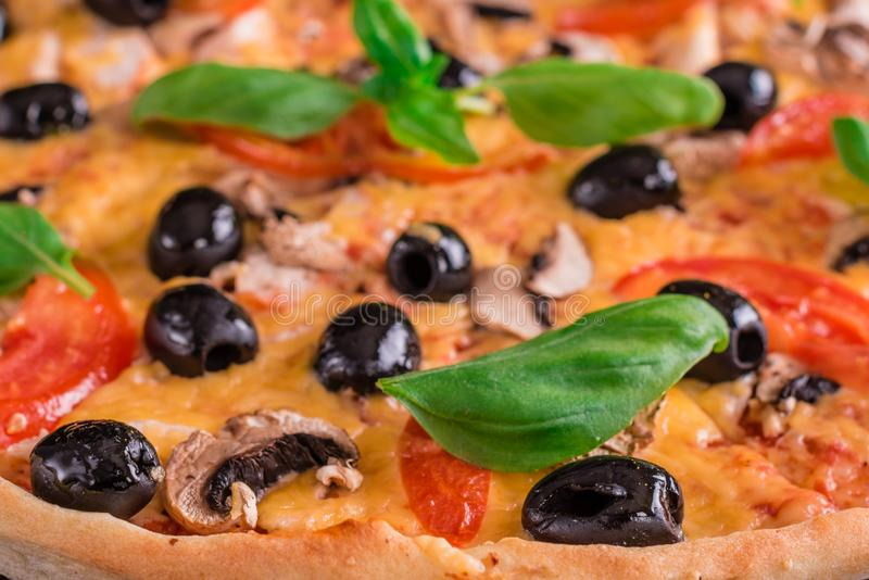 Tasty fresh hot pizza against a dark background. Pizza, food, vegetable, mushrooms. It can be used as a background royalty free stock images