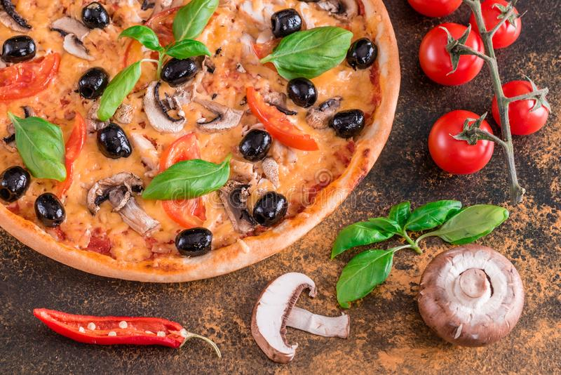 Tasty fresh hot pizza against a dark background. Pizza, food, vegetable, mushrooms. It can be used as a background royalty free stock photos
