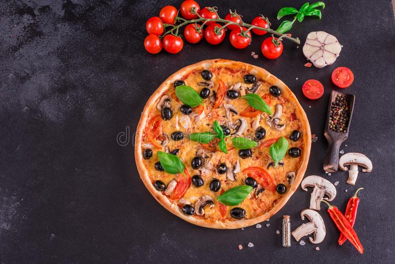 Tasty fresh hot pizza against a dark background. Pizza, food, vegetable, mushrooms. It can be used as a background royalty free stock image