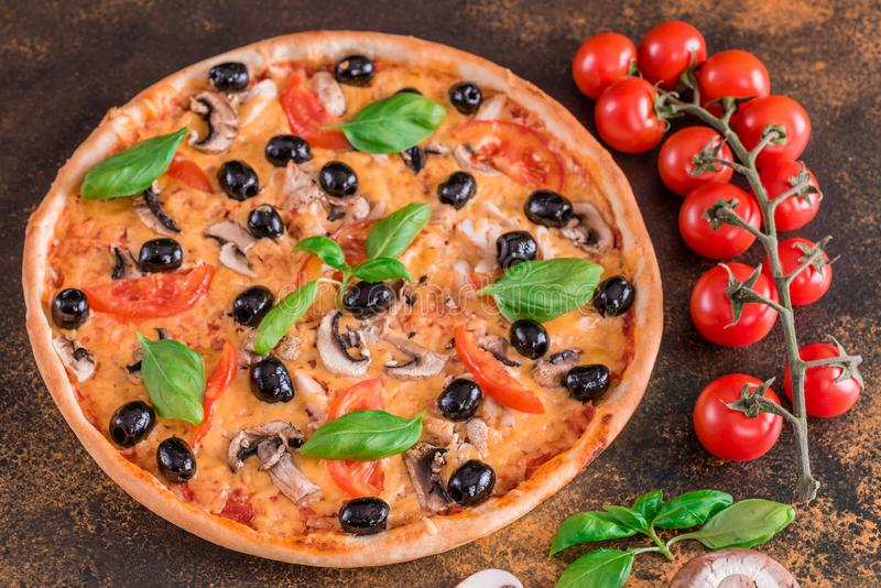 Tasty fresh hot pizza against a dark background. Pizza, food, vegetable, mushrooms. It can be used as a background royalty free stock photography