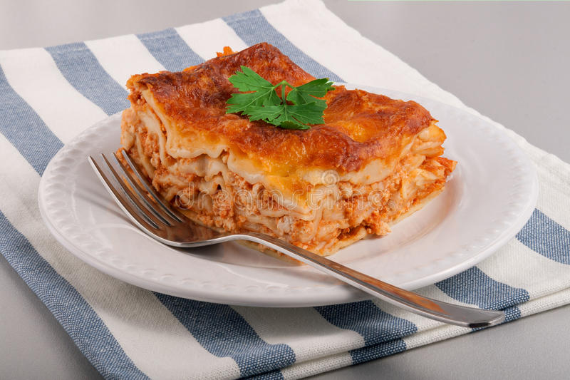 Tasty fresh lasagne on a white plate stock photo