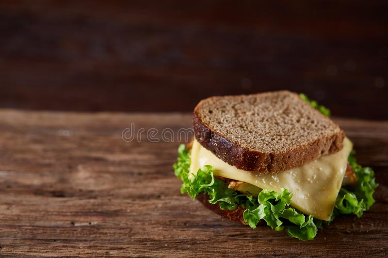 Tasty and fresh sandwiches on cutting board over a dark wooden background, close-up stock images