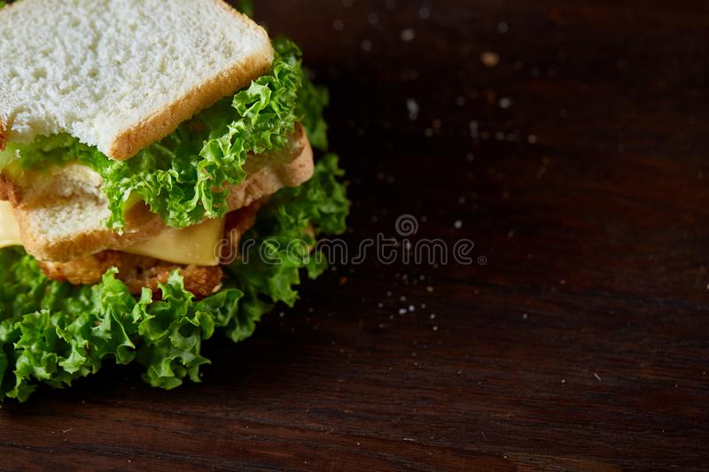 Tasty and fresh sandwiches on cutting board over a dark wooden background, close-up royalty free stock photography